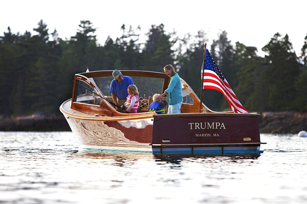 Senior couple show their two grandchildren how to fish, aboard a power yacht in Somes Sound, Maine, United States of America