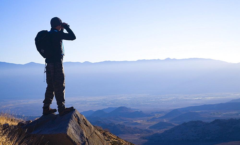 Hiker surveys his surroundings through binoculars. Photo by Thomas Kranzle, United States of America
