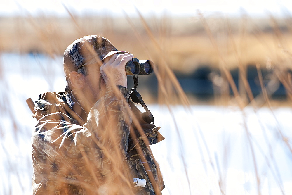 Brad Jackson uses binoculars scans the area for ducks in Carson City, NV, United States of America