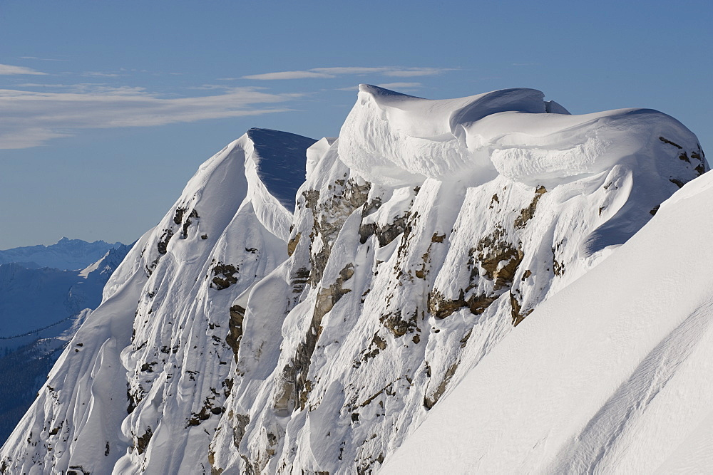 A mountain ridge holds heavy cornices from winter storms, Canada