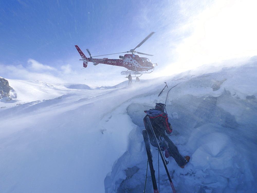 A mountain rescue technician is descending into a crevasse. When a skier breaks through the snow and tumbles down the glacier, the only way out is being winched out by the rescuers of Air Zermatt. - 857-91527