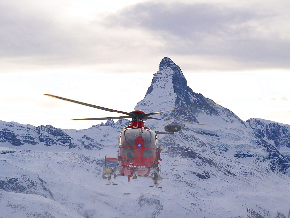 A rescue helicopter of type EC135  is approaching the scene of an accident in the mountains of Zermatt in the Swiss Alps. The famous Matterhorn mountain is in the background.