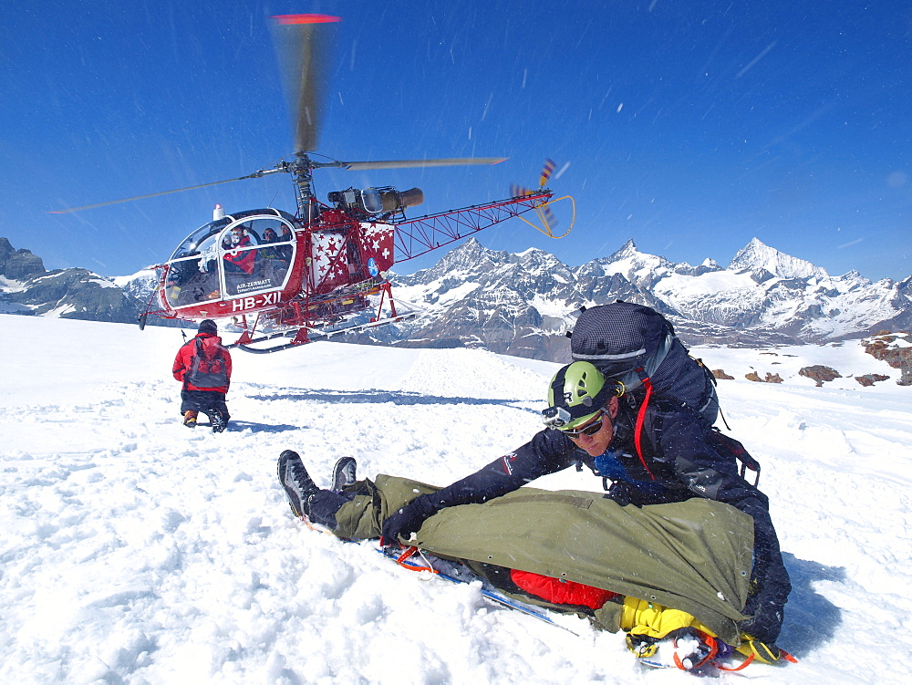 Mountain Rescue Personnel is helping an injured mountaineer in the Swiss Alps. A paramedic is covering the patient to protect it from blown up snow caused by the helicopter.