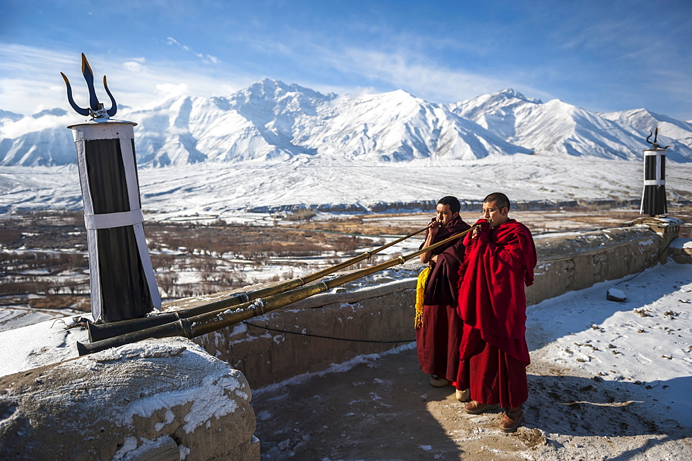 Two monks playing Tibetan trumpets (dungchen) on a roof of Spitok Monastery, Ladakh, India.