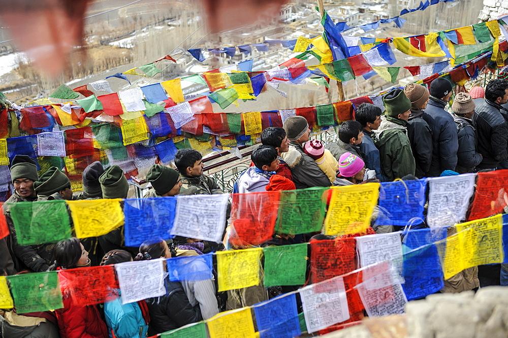 Pilgrims standing in line among prayer flags during Spitok Gustor festival, Spitok, Ladakh, India.