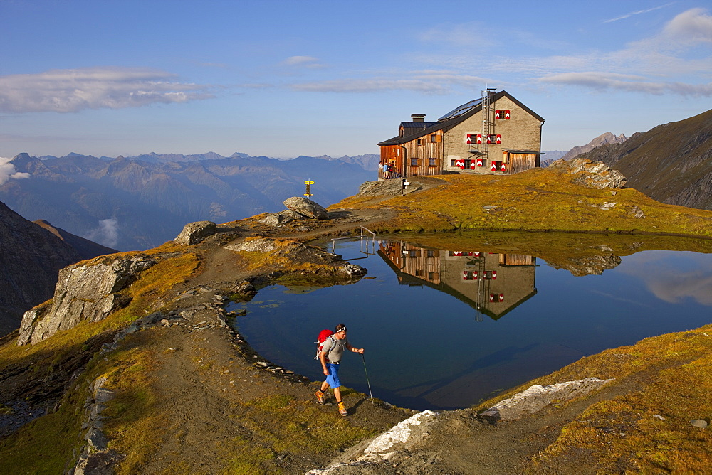 A male hiker at the lake of the Sudetendeutsche mountain hut during the Glocknerrunde, a 7 stage trekking from Kaprun to Kals around the Grossglockner, the highest mountain of Austria.