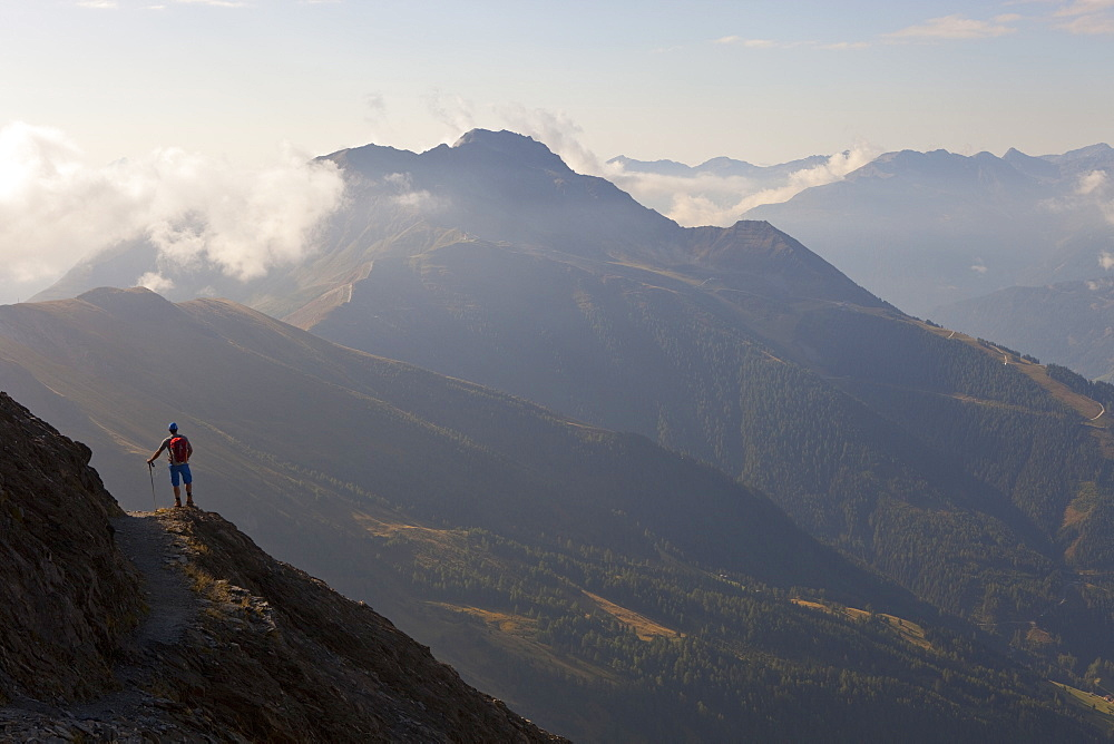 A male hiker enjoys the beautiful view over mountains and valleys, during the Glocknerrunde, a 7 stage trekking from Kaprun to Kals around the Grossglockner, the highest mountain of Austria.