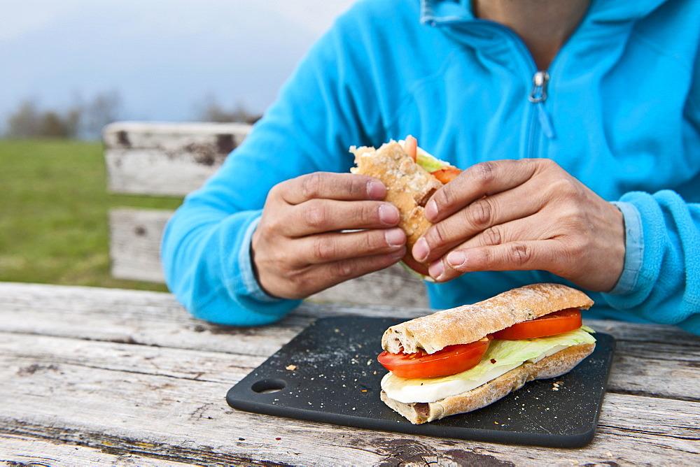 Woman eating a mozarella/tomato chiabatta at a picnic bench