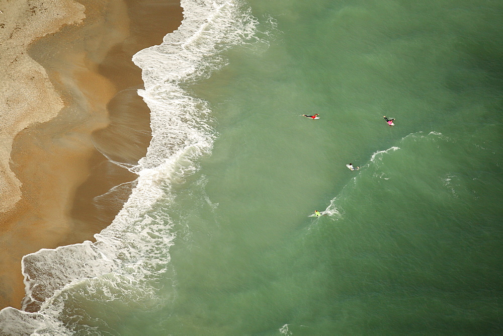 Aerial view of a surf contest, with four surfers in each heat in the water.