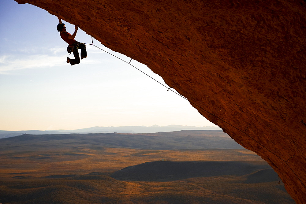 Rock Climber Swinging his feet while grabbing the rock.