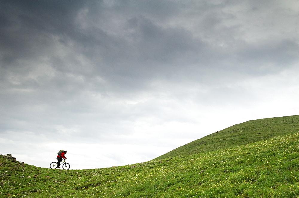 A man mountain biking across a green tundra scene in Colorado.