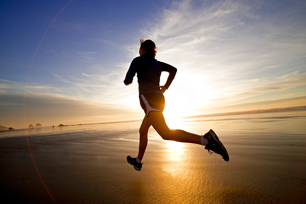 A woman jogs along the wet sand during a beautiful sunset.