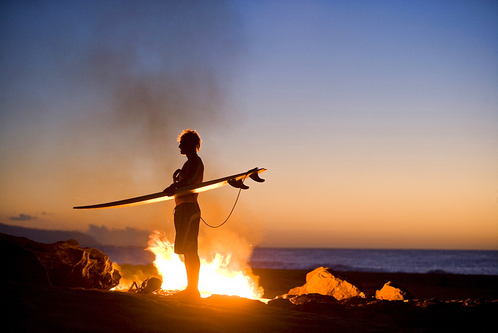 A surfer standing by a campfire on the beach in Hawaii.