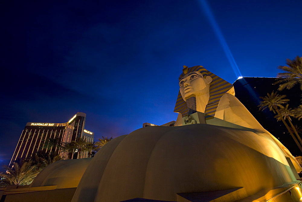 Huge foot of a Sphinx replica reaches towards you with Pyramid and light beam in background.