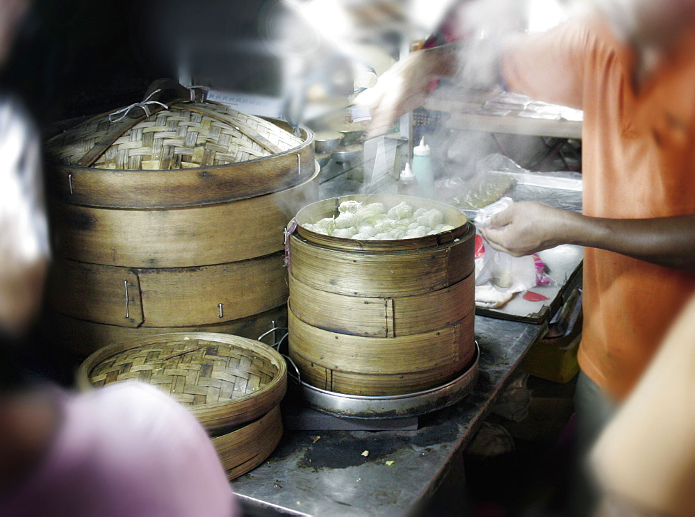 A street vendor sells dim sum at a night market known as Pasar Malam to the locals in Kuala Lumpur, Malaysia.