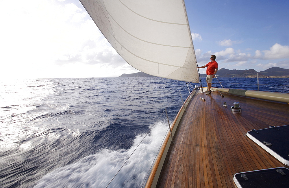 A man stands on the bow of a yacht while sailing near St. Bartholomew, French West Indies.