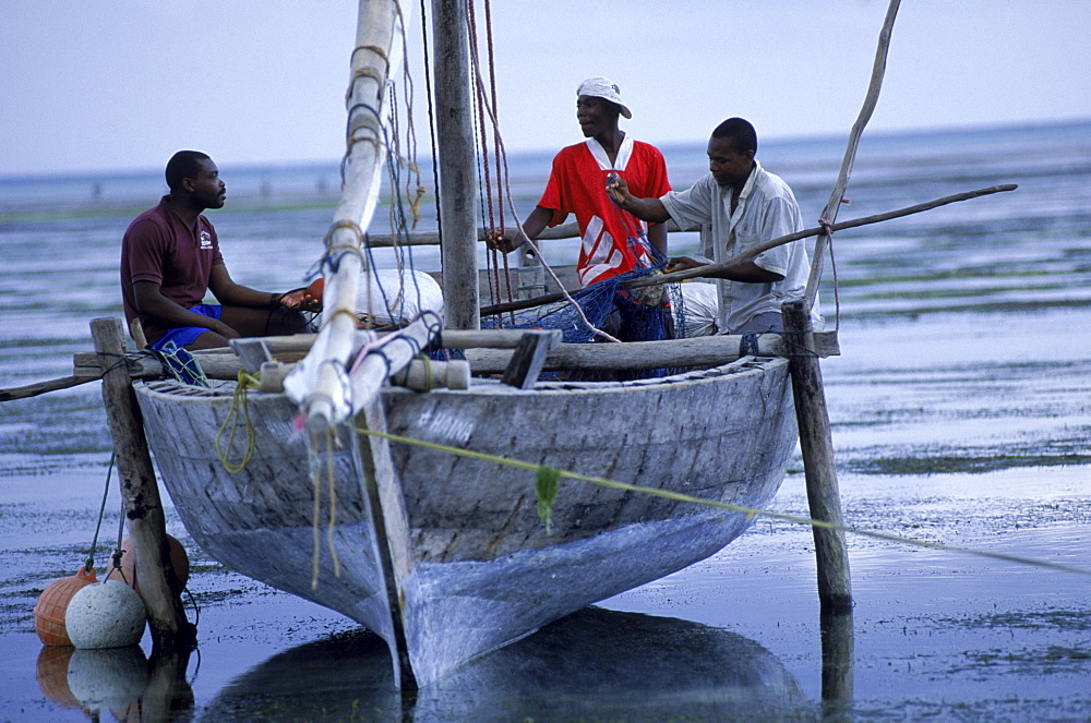 Fishermen sit in a beached dhow on the beach at Paje, on the east coast of Zanzibar Island, Tanzania.