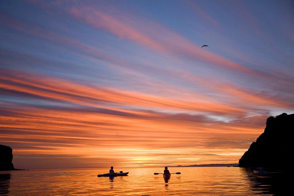 Two kayakers enjoy the orange sky at sunset along the coast of the Baja Peninsula, Loreto, Baja California Sur, Mexico.