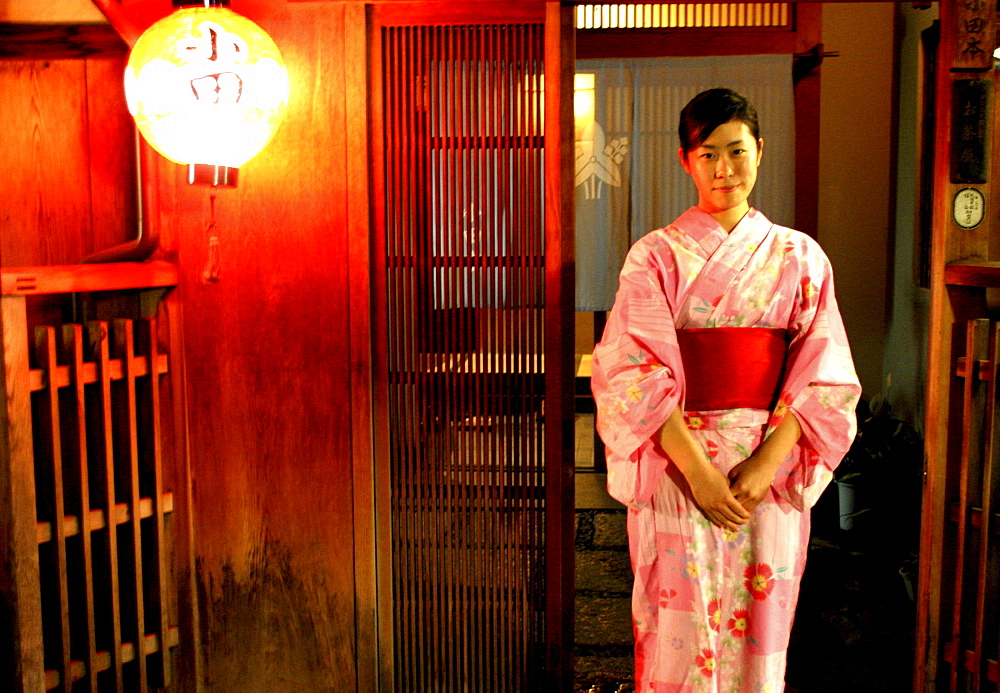 A young Geiko stands in front of the Okiya, (Geisha House), Kyoto, Japan.