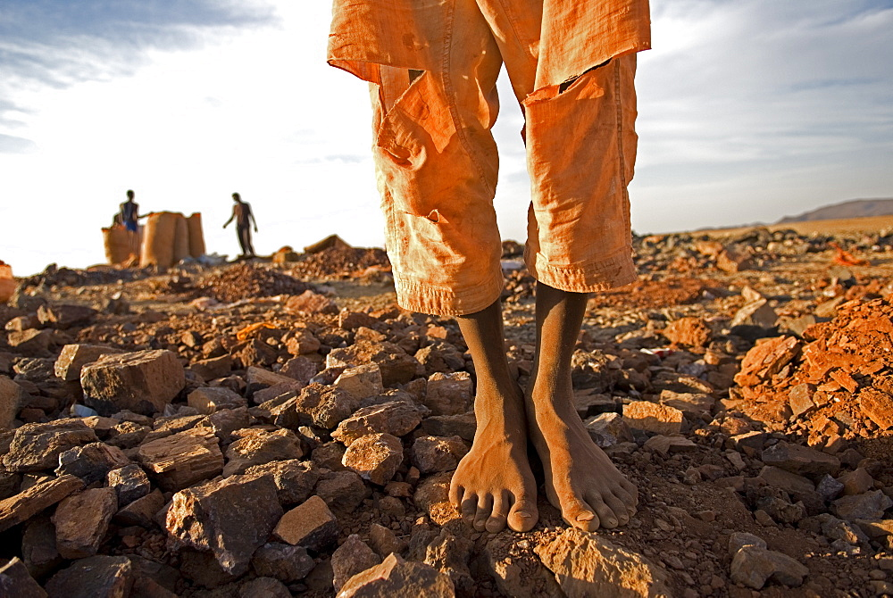 A barefoot goldmine worker stands near a shaft in Sudan.