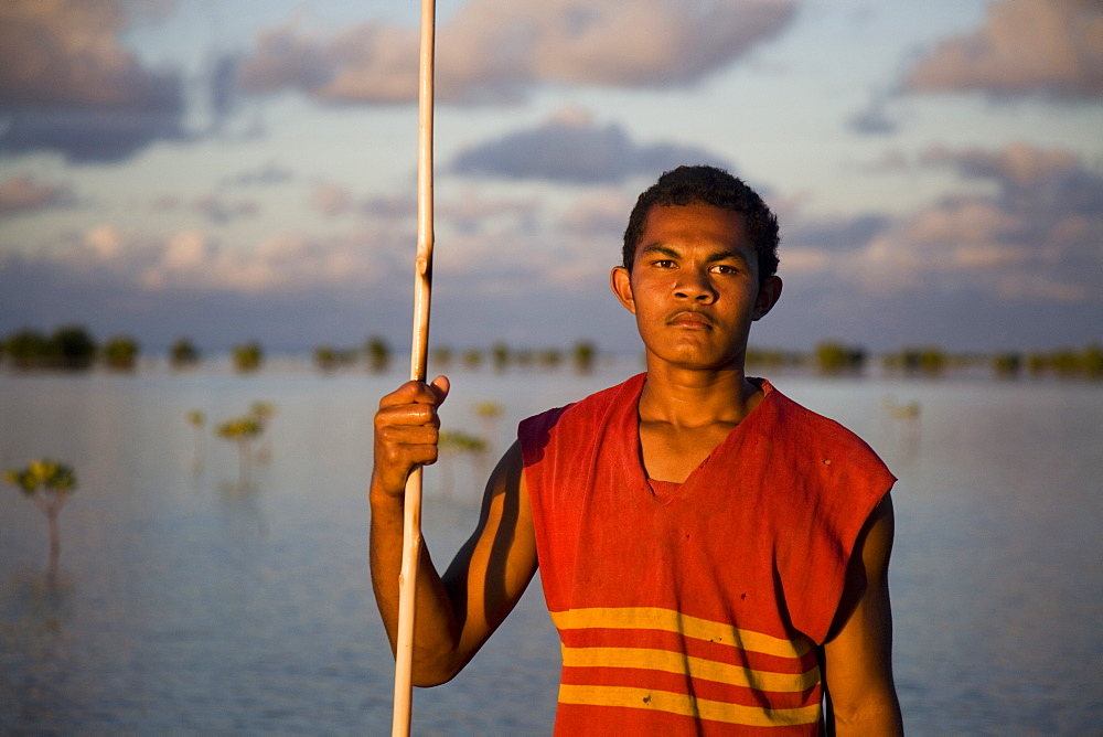 A man holds his spear as he fishes in the mangrove trees at dusk.