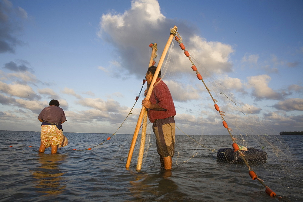 A man holds the ends of a net while a woman collects any trapped fish.