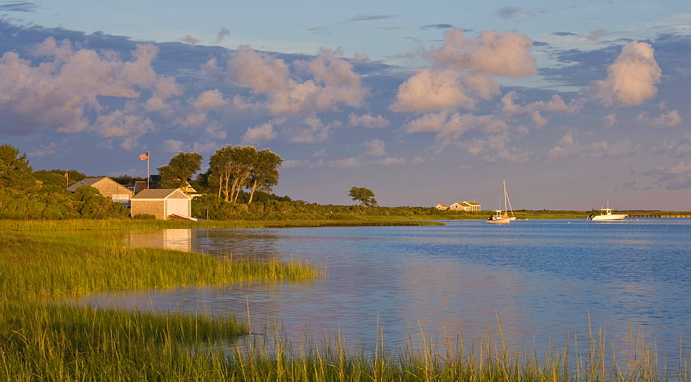 The sun rises over a small harbor where boats are anchored.