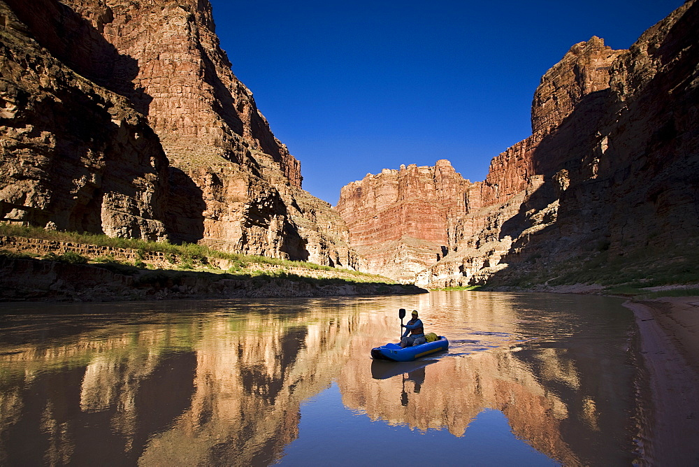 A person paddling an inflatable kayak duckie down the Colorado river, Utah.