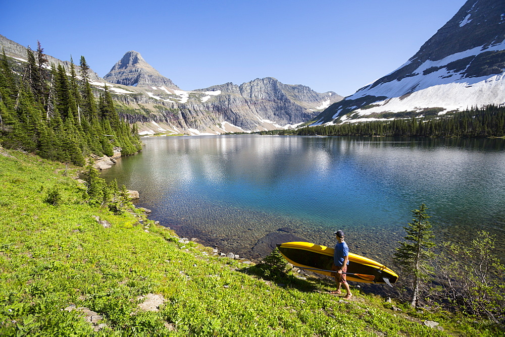 A man carries a portable stand up paddle board (SUP) at Hidden Lake in Glacier National Park.