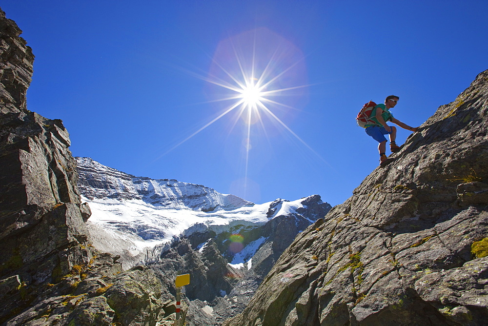 A male hiker climbs a rocky passage during the Glocknerrunde, a 7 stage trekking from Kaprun to Kals around the Grossglockner, the highest mountain of Austria.