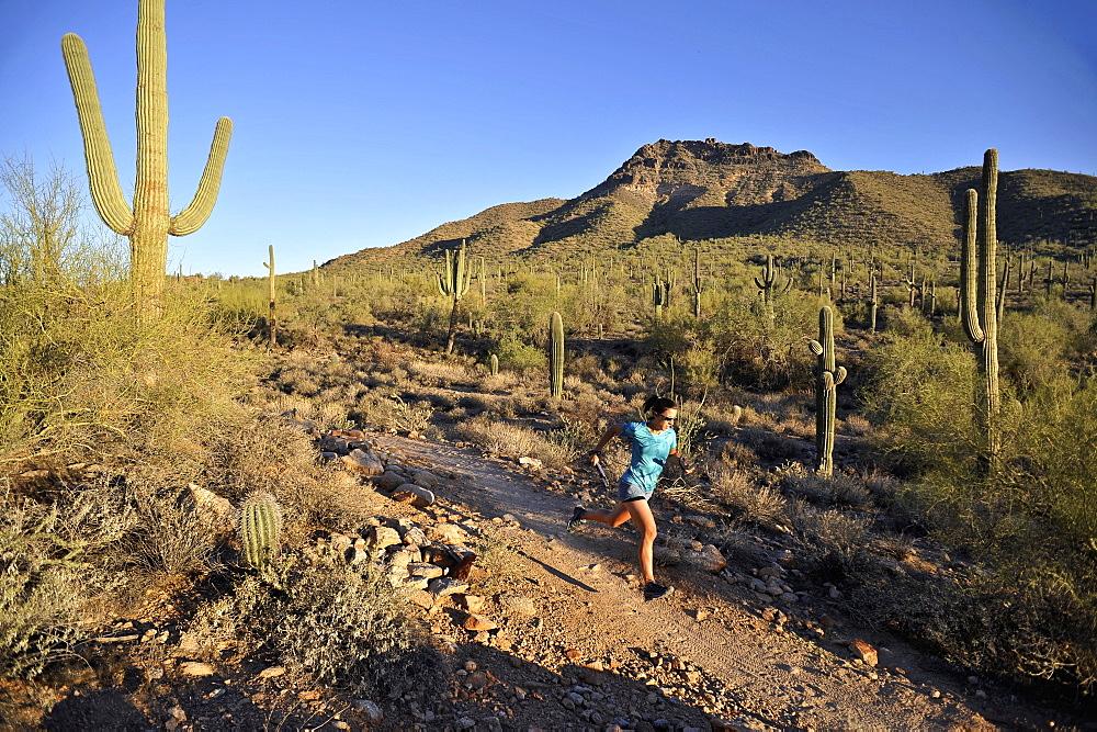Woman trail running in Usery Mountain Park, Phoenix, Arizona November 2011.