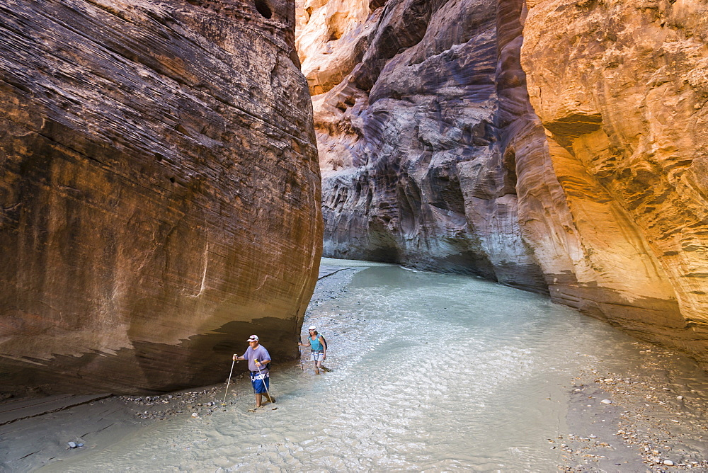 Two people hiking in a canyon with water in it.