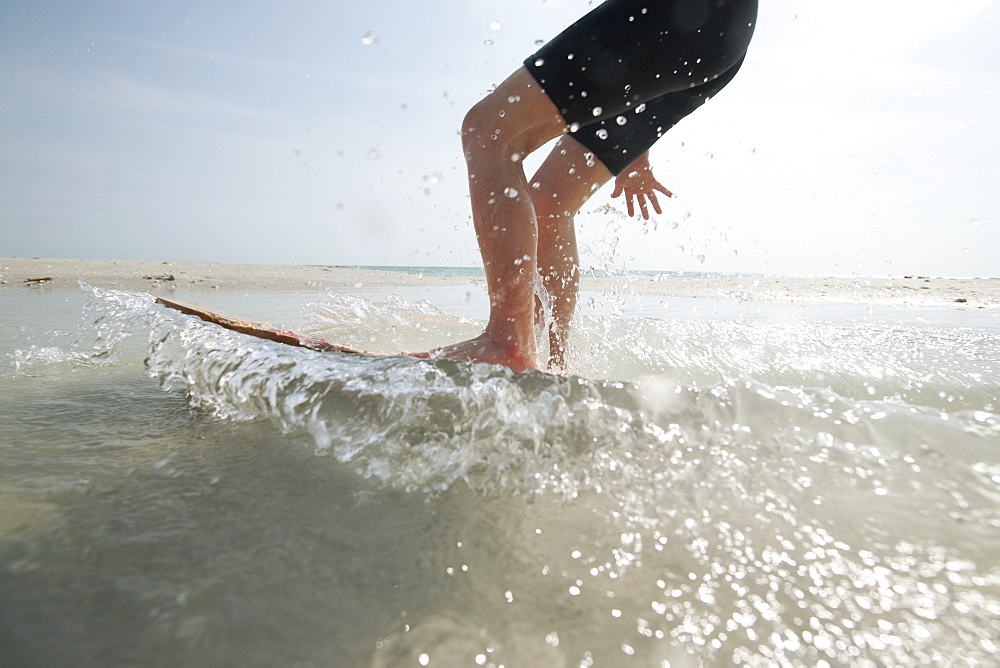 An action shot of a boy on a skim board at the shoreline.