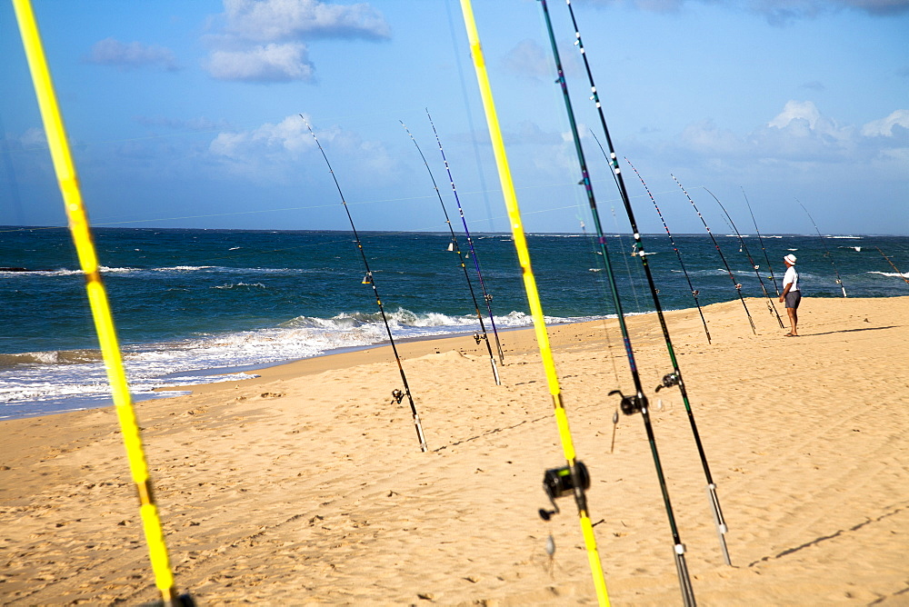 A man tends to his fishing rod on the beach.