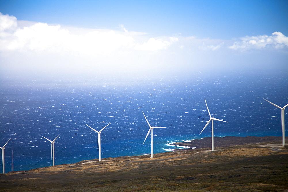 A row of huge wind turbines on a hillside.