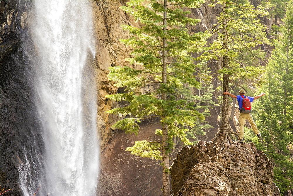 A man hiking below Treasure Falls, San Juan National Forest, Pagosa Springs, Colorado.