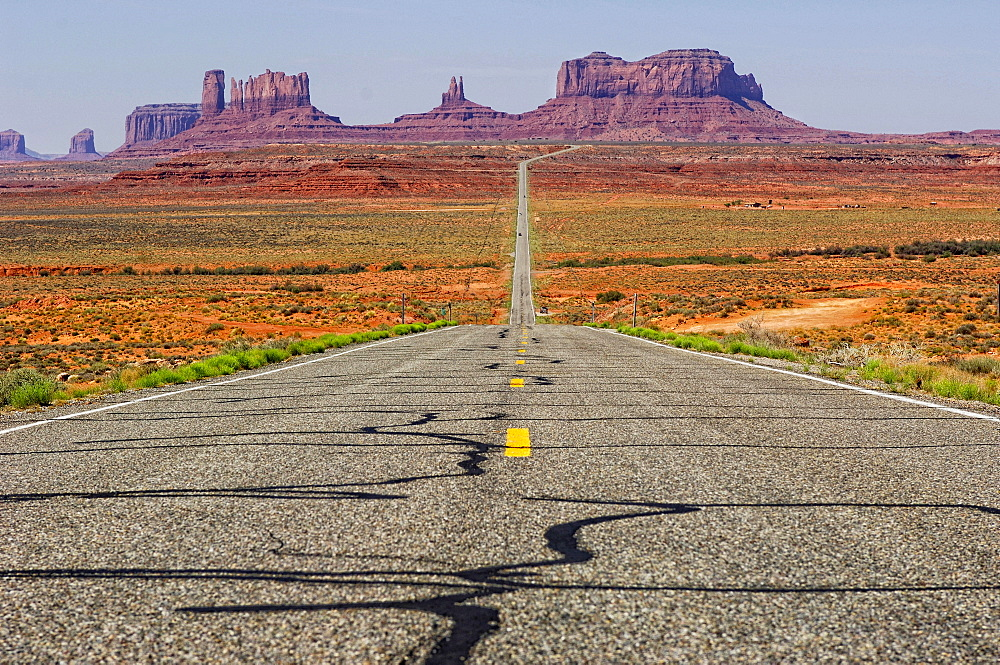The road that leads to Monument Valley Navajo Tribal Park curves down and then back up again as it approaches the sandstone sculptures that make up the park in Mexican Hat, Utah - 857-92586