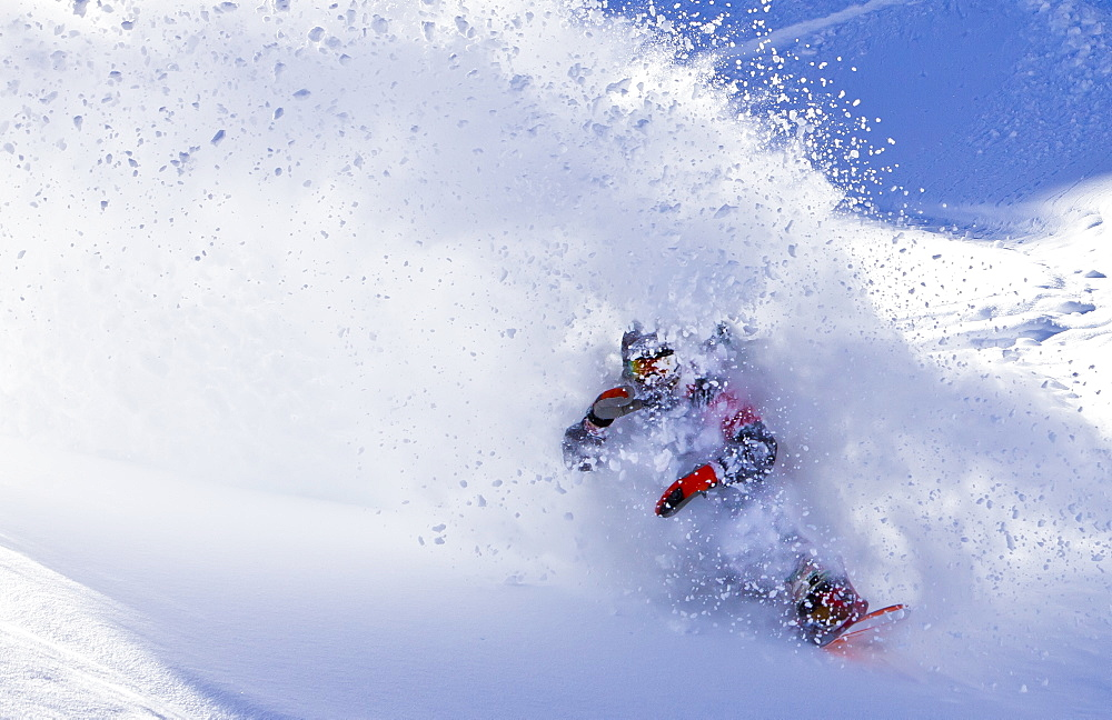 A man slashes deep snow on his snowboard and comes through the resulting powder cloud.