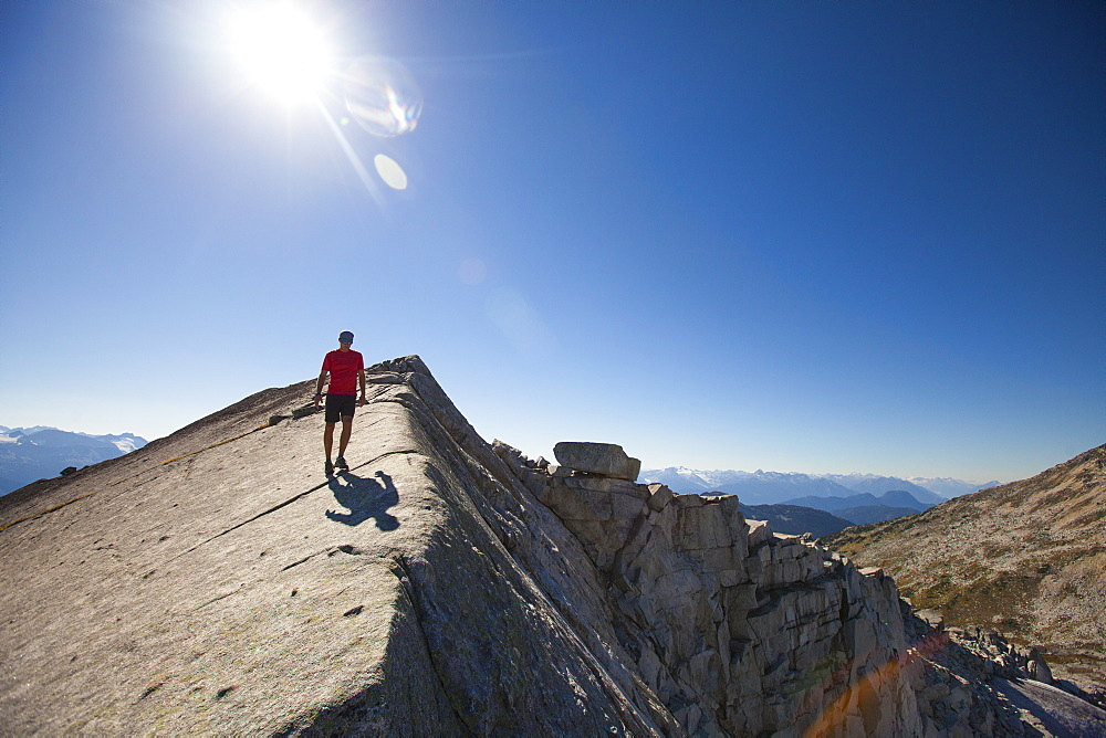 A hiker walks across a rocky slab ridge near the summit of Cassiope Peak, Pemberton, British Columbia, Canada.