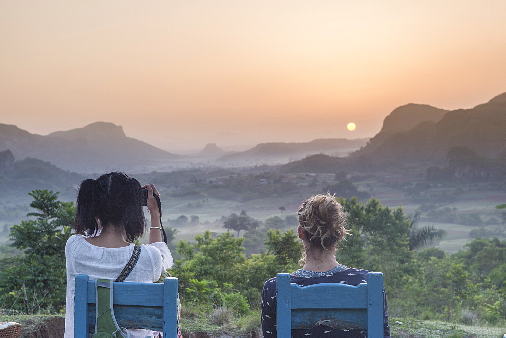 Two girls sitting on wooden chairs watching the sunrise above Vinales National Park from Los Acuaticos, the final point of an early morning trekking famous to watch the sun rising. Vinales, Cuba