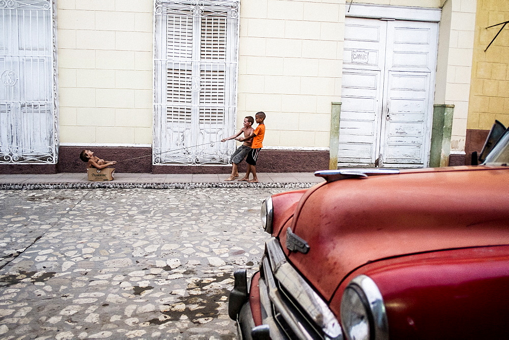Three kids play on the street in front of a red classic car in Trinidad, Cuba
