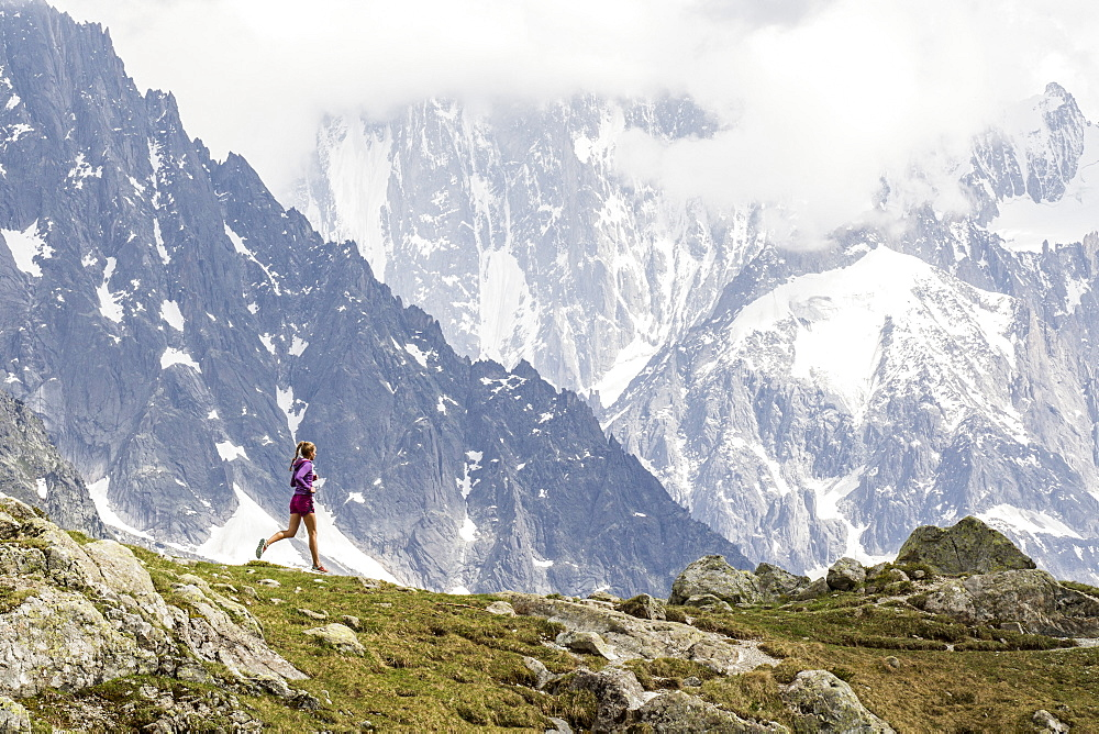 Girl trail running in Chamonix around the Chesery lake, Les des Cheserys, Haute Savoie, France.