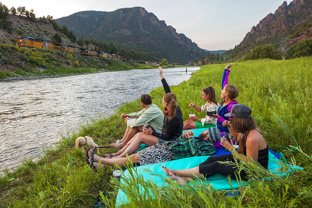 Boaters wave at a passing freight train while eating dinner by the Upper Colorado River at the Benches Campground near Kremmling, Colorado.
