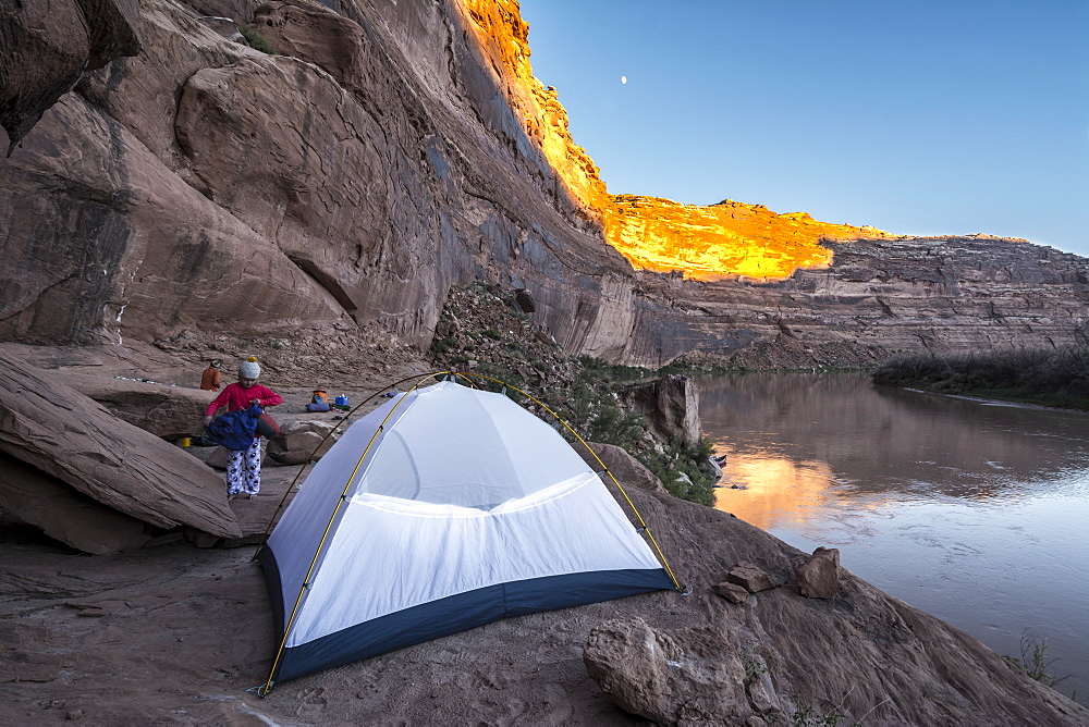 A young girl getting ready for bed in a tent while camping on sandstone along the Labyrinth Canyon section of the Green RIver, Green River, Utah.