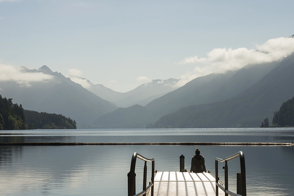 A woman sits on the end of a dock overlooking Lake Crescent in Olympic National Park, Washington on June 4, 2014.