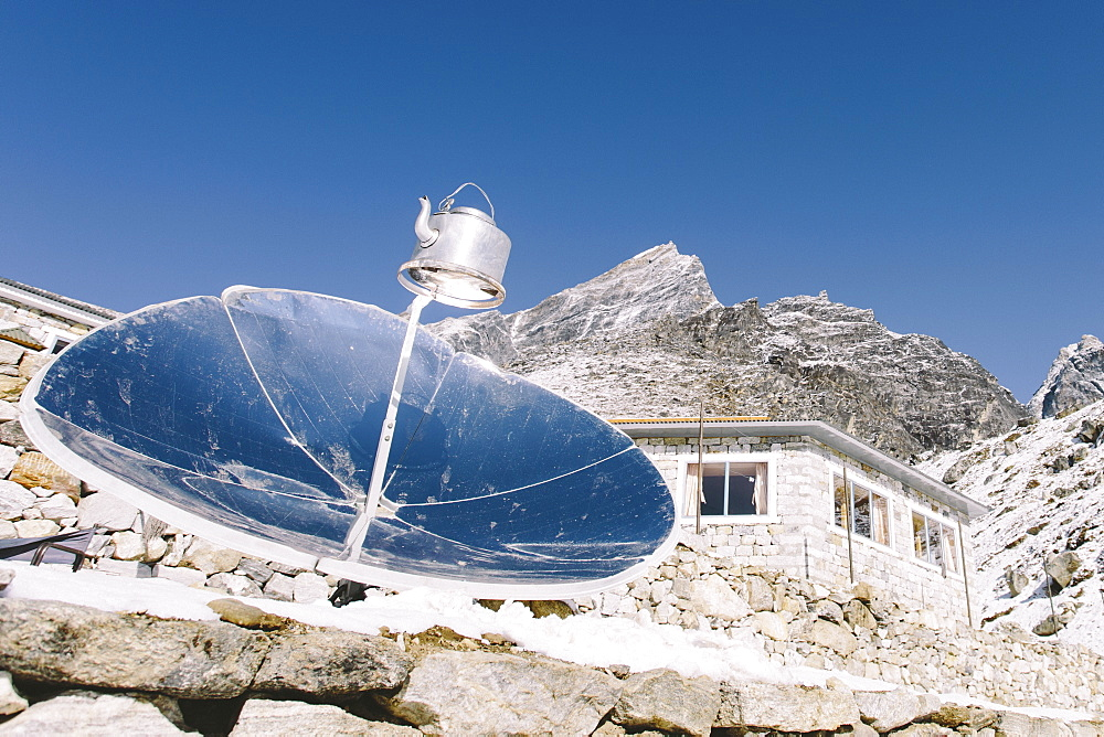 A reflector boils water in a kettle at high altitude in Nepal's Everest Region.