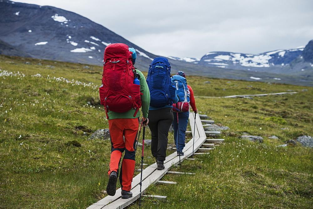 Hikers walk on wooden planks between Alesjaure and Tjäktja, Kungsleden trail, Lapland, Sweden - 857-92930