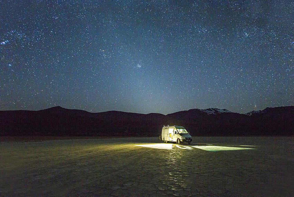 A white van is parked in a giant dried lake bed at night under a starry, Milky Way sky with what appears to be a halo of light around the van.