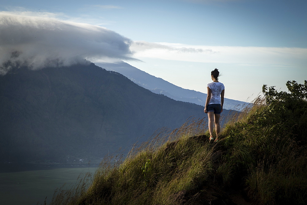Woman standing on mountain overlooks volcano at sunrise on Bali - 857-92960