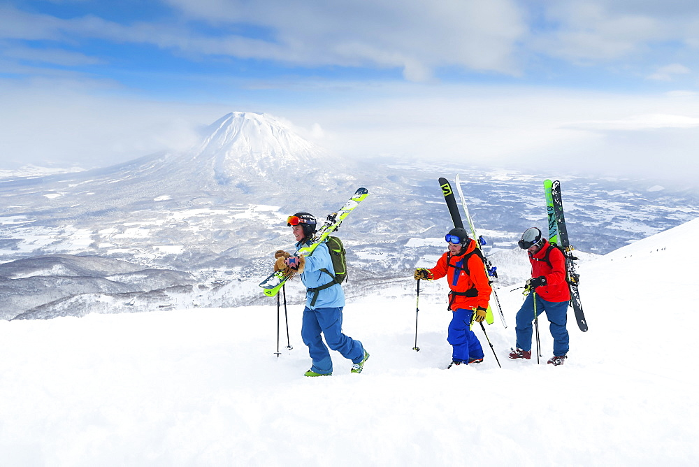 "With the volcano Yotei in the background a female and two male backcountry skiers are hiking to the summit of mount Annupuri, in the ski resort Niseko United on the Japanese island of Hokkaido. Niseko United is comprised of four resorts on the one mountain, Annupuri (1,308m). 100km south of Sapporo, Niseko Annupuri is a part of the Niseko-Shakotan-Otaru Kaigan Quasi-National Park and is the most eastern park of the Niseko Volcanic Group. Hokkaido, the north island of Japan, is geographically ideally located in the path of consistent weather systems that bring the cold air across the Sea of Japan from Siberia. This results in many of the resorts being absolutely dumped with powder that is renowned for being incredibly dry. Some of the Hokkaido ski resorts receive an amazing average of 14-18 meters of snowfall annually. Niseko is the powder capital of the world and as such is the most popular international ski destination in Japan. It offers an unforgettable experience for all levels of skier and snowboarder. Mount Yotei in the background is often referred to as the ""Mount Fuji of Hokkaido""."